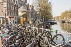 AMSTERDAM, DIE NIEDERLANDE - 22. APRIL: Fahrräder auf Brücke im April Lizenzfreie Stockbilder