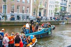 AMSTERDAM, DIE NIEDERLANDE 27. APRIL: Frohe Naturen in der Orange haben Spaß auf einem Boot während Day 27,2015 Königs im April stockfoto