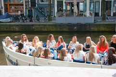 AMSTERDAM, DIE NIEDERLANDE 27. APRIL: Groupe von lokalen Mädchen feiern Day Königs in einem Boot 27,2015 im April in Amsterdam, d Lizenzfreies Stockbild