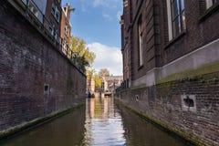 AMSTERDAM, DIE NIEDERLANDE - 14. APRIL 2019: H?user und Boote auf Amsterdam-Kanal stockfoto