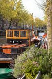 AMSTERDAM, DIE NIEDERLANDE - 13. APRIL 2019: H?user und Boote auf Amsterdam-Kanal lizenzfreie stockbilder