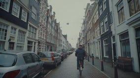 AMSTERDAM, DIE NIEDERLANDE - 26. DEZEMBER 2017 Bemannen Sie das Radfahren entlang typische Straße der Stadt Stockbild