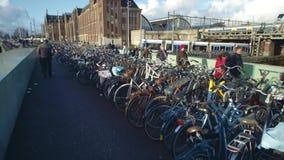 AMSTERDAM, DIE NIEDERLANDE - 26. DEZEMBER 2017 Großes Fahrradparken und bewegliche Tram und Zug in der Stadt Lizenzfreies Stockbild