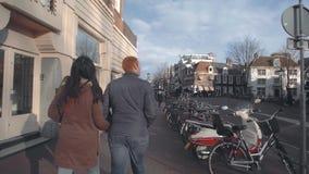 AMSTERDAM, DIE NIEDERLANDE - 26. DEZEMBER 2017 Junge Paare, die entlang typische Straße in der Stadt gehen Stockfotos