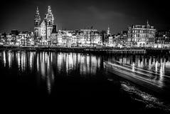 AMSTERDAM, DIE NIEDERLANDE - 14. DEZEMBER 2015: Schwarz-weißes Foto des Kreuzfahrtbootes Nachtkanäle von Amsterdam weiter gehend Stockfotografie