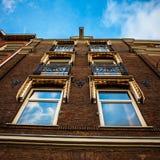 AMSTERDAM, DIE NIEDERLANDE - 15. JANUAR 2016: Berühmte Gebäude der Amsterdam-Stadtzentrumnahaufnahme zu gesetzter Zeit der Sonne  Lizenzfreies Stockbild