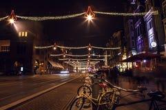 AMSTERDAM, DIE NIEDERLANDE - 20. JANUAR 2016: Nachtstraßen von Amsterdam mit unscharfen Schattenbildern von Passanten am 20. Janu Stockbild