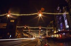 AMSTERDAM, DIE NIEDERLANDE - 20. JANUAR 2016: Nachtstraßen von Amsterdam mit unscharfen Schattenbildern von Passanten am 20. Janu Lizenzfreie Stockfotos