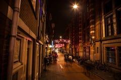 AMSTERDAM, DIE NIEDERLANDE - 20. JANUAR 2016: Nachtstraßen von Amsterdam mit unscharfen Schattenbildern von Passanten am 20. Janu Stockfoto