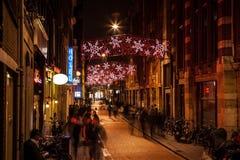 AMSTERDAM, DIE NIEDERLANDE - 20. JANUAR 2016: Nachtstraßen von Amsterdam mit unscharfen Schattenbildern von Passanten am 20. Janu Lizenzfreie Stockfotografie