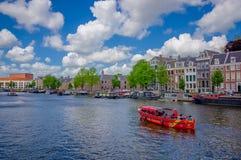 Amsterdam, die Niederlande - 10. Juli 2015: Der große Wasserkanal, der durch Stadt mit einigen Booten läuft, parkte längsseits Stockfotos