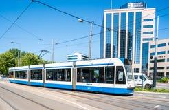 Amsterdam, el 7 de mayo de 2018 - tranvía con los pasajeros que pasan en el pecado del ` foto de archivo libre de regalías
