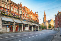 Amsterdam gata med domkyrkan Westerker på soluppgång, Netherland royaltyfria foton
