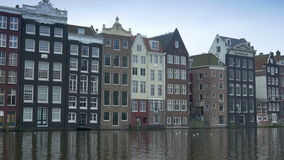 Amsterdam with historic canal houses 4K. Perspective shot of a canal in Amsterdam with dutch historic houses. The Netherlands stock video footage