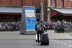AMSTERDAM, holandie - CZERWIEC 25, 2017: Turyści z wielkim bagażem zdosą krzyżować drogę w Amsterdam Zdjęcie Stock