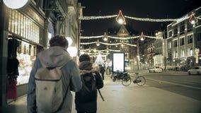AMSTERDAM holandie - GRUDZIEŃ 25, 2017 Turyści z plecakami chodzą wzdłuż miasto ważnej ulicy dekorującej dla Zdjęcie Stock