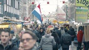 AMSTERDAM holandie - GRUDZIEŃ 27, 2017 Twierdzi flaga nad zatłoczoną turystyczną ulicą w centrum miasta Zdjęcie Royalty Free