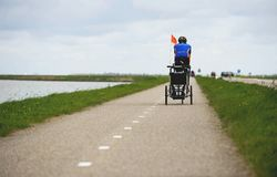 AMSTERDAM, holandie, Kwiecień 2017: Mężczyzna na roweru ciągnięcia dziecka furze dla Rowerowego rydwanu Thule Rowerowa ścieżka z  zdjęcie royalty free