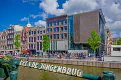 Amsterdam, holandie - Lipiec 10, 2015: Tradycyjni Holenderscy bloki mieszkalni z powabnymi czerwonymi ceglanymi domami obok wody Fotografia Stock