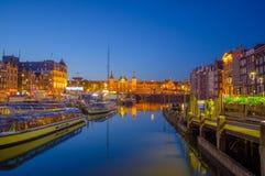 Amsterdam, holandie - Lipiec 10, 2015: Wodni kanały nocą, pięknym zmrokiem i miast światłami na obich stronach, - niebieskie nieb Fotografia Royalty Free