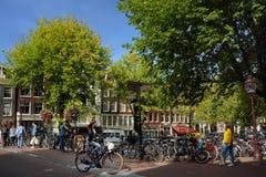 AMSTERDAM, holandie - WRZESIEŃ 17, 2018: Ulica, budynki, kanał, most z bicyklami, zaludnia Typowy rozdroże zdjęcie royalty free