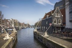 Typical old Amsterdam buildings along the canal. People on the benches. Tulips in tubs Stock Photos