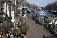 Typical old Amsterdam buildings along the canal. People on the benches. Tulips in tubs Stock Photo