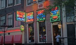 Colorful neon signs promoting Red Light Bar in city`s red light district Royalty Free Stock Photography