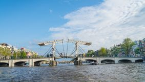 Vintage private VIP canal cruise boat passes through Magere Brug, Skinny Bridge on the Amstel River. AMSTERDAM, HOLLAND - AUGUST 17, 2017; small vintage private stock photos