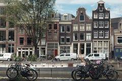 AMSTERDAM HOLLAND - Juli 24, 2017: invallning av gamla Amsterdam med parkerade cyklar och danshus Royaltyfri Fotografi