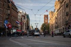 AMSTERDAM HOLLAND - MAJ 13: Spårvagnspring i stadsmitten bland gångare Arkivbilder