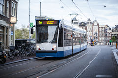 AMSTERDAM, HOLLAND - MAY 13: Tram running in the city centre amongst pedestrians. Royalty Free Stock Photo