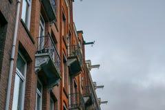 Amsterdam hus med balkonger och krokar arkivbild