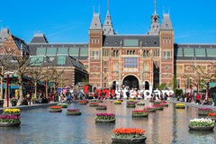 Amsterdam, I Amsterdam sign with Rijksmuseum at the back. Sign of I amsterdam at the front of Rijksmuseum and an artificial pond with tulip flowers floating on Stock Images