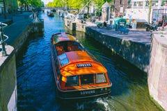 Amsterdam-Kan?le und -leute, die Reserve auf ihren Booten an einem sonnigen Tag genie?en lizenzfreie stockfotos