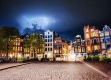 Amsterdam-Kanal an den schönen Kumuluswolken und -blitz Die Stadt ist das Kapital und die meiste einwohnerstarke Stadt in Stockfotografie