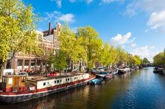 Amsterdam-Kanal mit Booten entlang der Bank des Flusses während des sonnigen Tages, die Niederlande Stockbilder