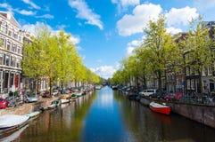 Amsterdam-Kanal mit Booten entlang der Bank während des sonnigen Tages, die Niederlande Lizenzfreies Stockbild