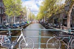 Amsterdam-Kanal mit Fahrrädern auf der Brücke und den parkendes Auto entlang der Bank netherlands Lizenzfreie Stockfotos