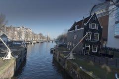 Amsterdam kanal och byggnader och av vertikal byggnad Arkivfoto