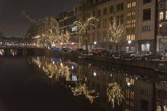 Amsterdam kanal och byggnader på natten Arkivbild