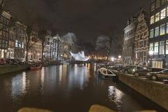 Amsterdam-Kanal und -gebäude nachts Stockbilder