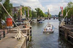 Amsterdam kanaler med broar, fartyg och hus Royaltyfria Bilder