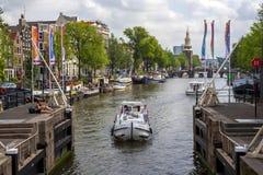 Amsterdam kanaler med broar, fartyg och hus Royaltyfri Foto