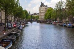 Amsterdam kanaler med broar, fartyg och hus Arkivfoto