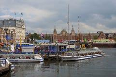 Amsterdam kanaler med broar, fartyg och hus Arkivbild