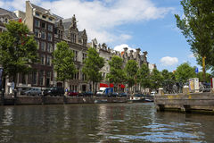 Amsterdam kanaler med broar, fartyg och hus Arkivfoton