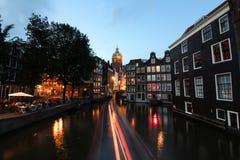 Amsterdam kanaler och härliga byggnader nära floden på, lång exponering för afton royaltyfria foton