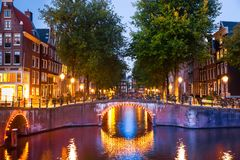Amsterdam kanaler på solnedgången med ljus royaltyfri fotografi