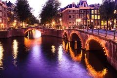 Amsterdam kanaler på solnedgången med ljus arkivfoto
